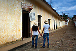 Young Colombian couple study a menu at a restaurant on the cobblestone streets of the colonial town of Guane.