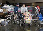 Hungry residents fill a shopping trolley full with food and other items from an abandoned supermarket that was badly damaged by the March 11 earthquake and tsunami in Ishinomaki, Japan on 15 March, 2011.  A local government official said that rumors of theft from abandoned shops and residences had been reported after food and drink supplies in the city ran low.  Photographer: Robert Gilhooly