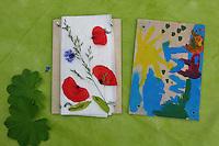 Blumenpresse, Kinder haben aus Brettern, Papier und Flügelschrauben eine Pflanzenpresse gebastelt und bunt bemalt und trocknen Mohn, Kornblume und Gras für ein Herbarium