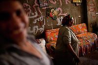 2011 Mokattam Garbage City (alla periferia del Cairo) il quartiere copto dove si vive in mezzo alla spazzatura raccolta:donne e sullo sfondo iconografia cristiana,(on the outskirts of Cairo) the Coptic quarter where people live in the midst of garbage collection: women and Christian iconography in the background.