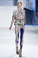 Julia Nobis walks runway in an indigo psychedelic printed chiffon V-neck top with printed stretch cotton criss cross cutaway overlay and peplum belt, and indigo psychedelic printed stretch cotton legging.by Vera Wang, for the Vera Wang Spring 2012 collection, during Mercedes-Benz Fashion Week Spring 2012.