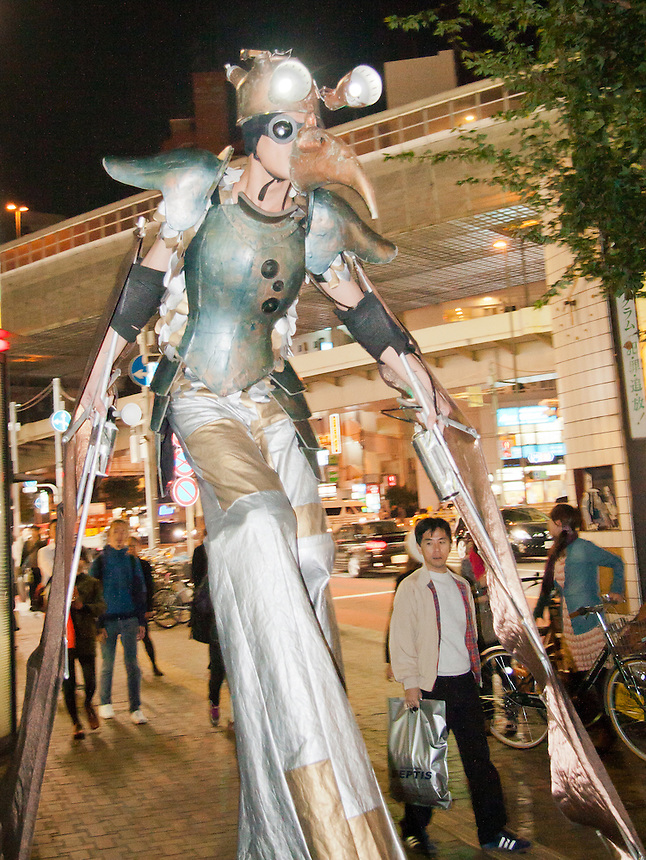 "You can find some very strange people on the streets of Tokyo at night.This stilted street performer is wearing a ""bird"" costume."