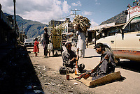 A men and a young boy painting Butt's for new made rifles in the main street of Darra. Darra town in Pakistan clandestinely provides arms to more than eight Central Asian countries.