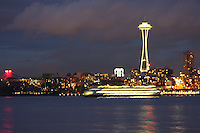 The Washington State ferry run to Bremerton pulls away from the Emerald city with Seattle Center and the needle alight in the background.