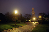 Newport, RI USA - Gas lamps light a night time view of Trinity Church and Queen Anne's square park with no electric lights...