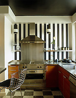 A professional style oven and extractor stand against a dramatic black and white striped wall in this cherry-wood kitchen