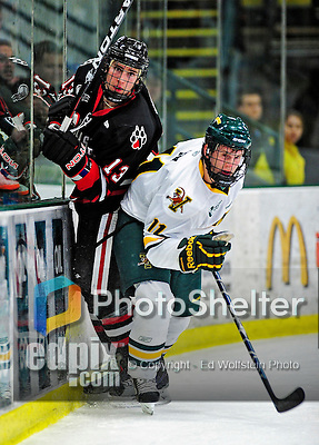 26 November 2010: University of Vermont Catamount forward H.T. Lenz (11), a Freshman from Vienna, VA, checks Northeastern University Huskies' defenseman Randy Guzior (13), a Senior from Lemont, IL, at Gutterson Fieldhouse in Burlington, Vermont. The Huskies came back from a 2-0 deficit to earn a 2-2 tie against the Catamounts. Mandatory Credit: Ed Wolfstein Photo
