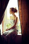 Portrait of young woman in dress sitting in window sill