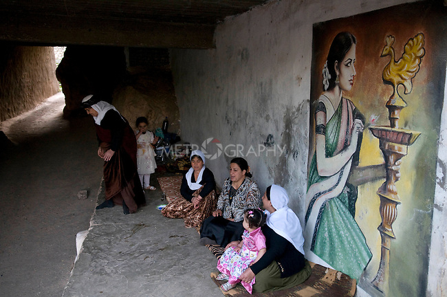 LALISH VALLEY, IRAQ: Yezidi women sit by a painting in the Lalish Temple as they wait for the sun to set to begin their New Year's celebration.  The painting depicts a Yezidi woman praying to the sacred peacock...The Yezidis, a minority religious group found in northern Iraq, celebrate Chwar Shema Sur (Red Thursday), as part of their New Year festival.  The Yezidis are the religious descendants of Zoroastrians and as a religious minority in Iraq are often targeted by terrorists.