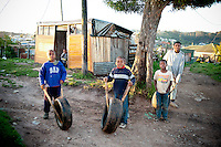 Young boys participate in a very popular pastime in many rural parts of South Africa. This involves two sticks and an old tire that leads to long hours of races and competition between themselves.