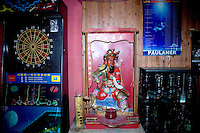 "A small shrine to Virupaksa, one of Buddhism four heavenly kings, sits next to a beer display case and dart board in Castle Bar in Nanjing, China.  Virupaksa is the West king and represents ""He who knows all"" in Buddhism."