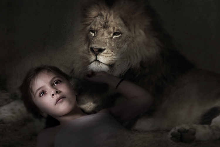 Child lying down with a lion in a dark place and light shining on her face.