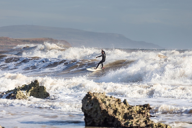 Surfers enjoying the Autumnal swells at Freshwater Bay on the Isle of Wight