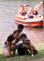 Billy Joe Nelson, left, the girlfriend of the victim(sp?), gets a hug from friend Mica Quick while holding her dog Deva who was in the canoe Thursday evening when it capsized. (photo..Andrew)