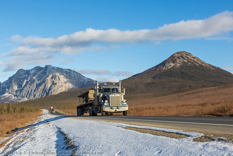 Truck travels the James Dalton highway with Mt. Sukakpak in the distance, Brooks range, Arctic, Alaska.
