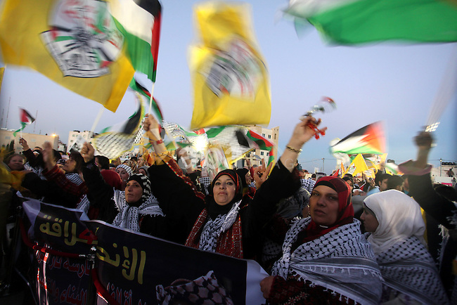 Palestinians wave their national flag during a rally on the eve of the 48th anniversary of the formation on the Fatah movement, on December 31, 2012, in the West Bank city of Ramallah. The Fatah anniversary commemorates the first operation against Israel claimed by its armed wing then known as Al-Assifa (The Thunderstorm in Arabic) on January 1, 1965. Photo by Issam Rimawi