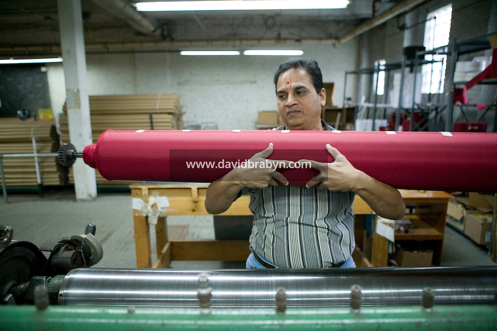 21 June 2005 - Oaks, PA - Suresh Patel lifts a roll of polyester fabric that will be turned into red stripes off a machine at the Annin & Co. American flag manufacturing plant in Oaks, PA, USA. Photo Credit: David Brabyn.