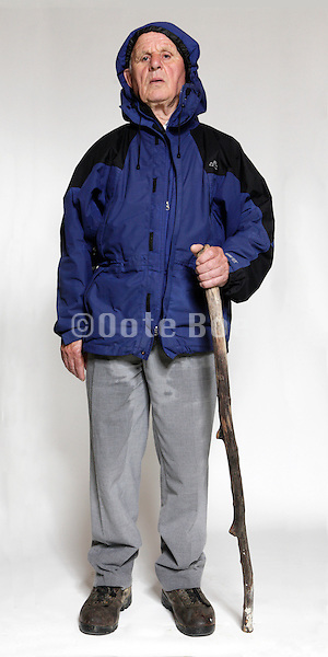 studio portrait of a senior man with walking stick wearing a parka