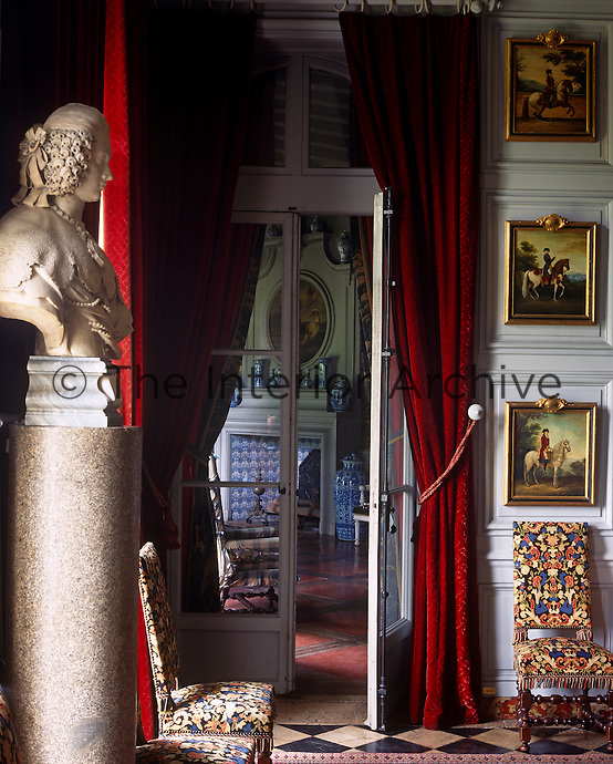 A trio of horse paintings hangs beside a double door dressed in heavy red curtains between two ante-rooms
