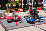 The Los Altos High School robot, #114, and Monte Vista High School robot, 100, hang from a pyramid structure as the driver and manipulator attempt to climb the robots higher.