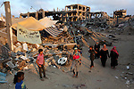 Palestinians walk past destroyed houses after returning home in the Tufah neighbourhood in eastern Gaza City on August 31, 2014. Calm returned to the coastal enclave in a August 26 ceasefire, and Gazans were gradually starting to rebuild their lives after a bloody and destructive 50-day war, the deadliest for years.. Photo by Ashraf Amra
