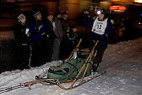 Crowds cheer as musher Tim Hunt of Skandia, Michigan rides through historic downtown Marquette, Mich. during the U.P. 200 Sled Dog Championship.