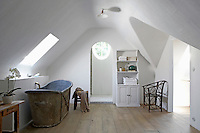 An antique zinc bath contrasts with a walk-in shower in this attic bathroom