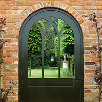 A view through the gothic panels in a garden door reveals the manicured lawn and trees beyond