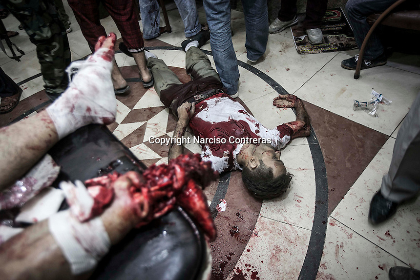 A dead body of a Syrian civilian lies down on the floor at the entrance of a hospital as other wounded civilians get emergency medical attention after have been killed or wounded in a simultaneous attack by heavy artillery shelling in different districts of Aleppo City.