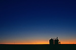 Sunset with silhouetted grain silo for crop storage Eastern Washington State USA.