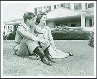BNPS.co.uk (01202 558833)<br /> Pic: RRAuction/BNPS<br /> <br /> Recently engaged John and Jackie relaxing in front of the Kennedy compound in Hyannis Port in the summer of 1953.<br /> <br /> Incredibly-rare photos highlighting the first foray into politics for John F. Kennedy that would eventually cost him his life have come to light.<br /> <br /> The 100 black and white snaps show a youthful-looking JFK from 1946, when he was campaigning to become a US congressman for the first time.<br /> <br /> The tragic future president is seen during an oration lesson where he was given help by an expert with public speaking and posture.<br /> <br /> The 29-year-old is also depicted mingling with the public at an annual parade and as well as celebrating his first political victory - a congressional primary vote - in June 1946.<br /> <br /> The images are being sold by US-based RR Auction.