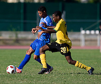 Shawn-Claud Lawson (20) of Jamaica tries to take the ball away from Jose Barralaga (13) of Honduras during the quarterfinals of the CONCACAF Men's Under 17 Championship at Catherine Hall Stadium in Montego Bay, Jamaica. Jamaica defeated Honduras, 2-1.