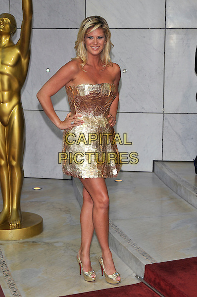 RACHEL HUNTER.World Music Awards 2010 at the Sporting Club Monte Carlo, Monaco..18th May 2010 .full length strapless shiny gold mini dress hands on hips tanned peep toe platform metallic shoes paillettes scales .CAP/PL.©Phil Loftus/Capital Pictures.