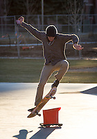Students practice at the skateboard park in late afternoon light.