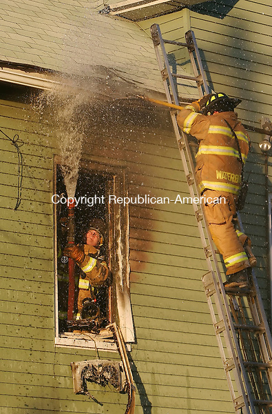WATERBURY, CT,  10 NOVEMBER 2006, 111006BZ01-  Waterbury firefighters overhaul the roof area outside a second floor window after fire damaged a Cherry Street home Friday.  <br /> Jamison C. Bazinet Republican-American