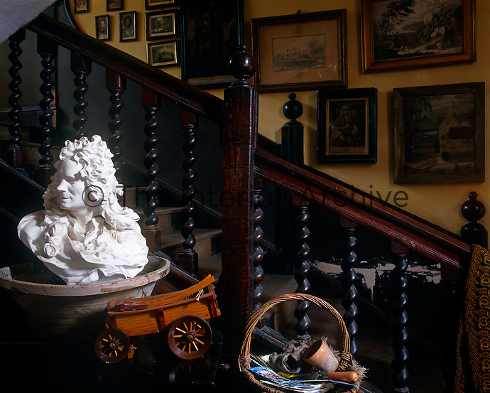 A bust inside a large ceramic pot clutters a table beside  the staircase