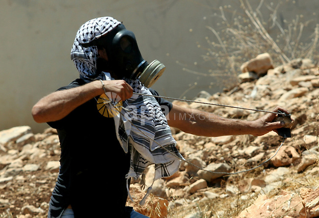 A Palestinian demonstrator throws stones towards Israeli border police during a protest against the expansion of the nearby Jewish settlement of Kdumim, in the northern West Bank village of Kufr Qaddum, on 06 July 2012. Photo by Nedal Eshtayah