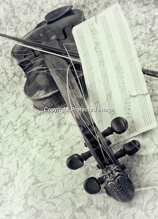 A broken antique violin and a piece of torn sheet music lay on a table.