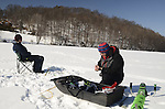 Men ice fishing on a hidden lake in Westchester New York - February 2015