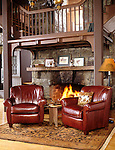 Hunting lodge fire place with two overstuffed leather easy chairs and brandy snifters
