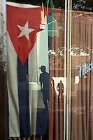 Pedestrians pass flags displayed in stopre windows in Santiago de Cuba Friday, where Fidel Castro and his band of insugents first appeared from the mountains on Jan. 1, 1959. Castro was scheduled to deliver a speach later that night.
