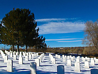 Headstones surrounded by snow at Fort Logan National Cemetery, Denver, Colorado.
