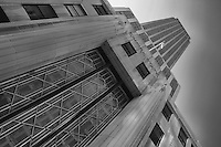 Looking up on an angle in black and white at the Empire State Building in NYC.