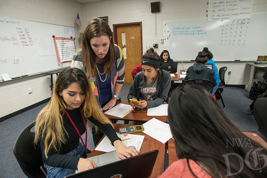 NWA Democrat-Gazette/ANTHONY REYES @NWATONYR<br /> Rachel Carethers, teacher on special assignment for secondary math, helps Carolina Ulloa, (from left) Abril Guerra and Maria Manjarrez work through a math problem Thursday, April 13, 2017 in their Algebra II class at Springdale High School. Carethers helps to implement a new style for teaching math that includes group work and cooperation.