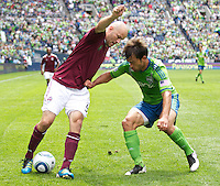 Colorado Rapids forward Conor Casey, left, and Seattle Sounders FC defender Patrick Ianni battle for the ball during play at CenturyLink Field in Seattle Saturday July 17, 2011. The Sounders won the game 4-3.
