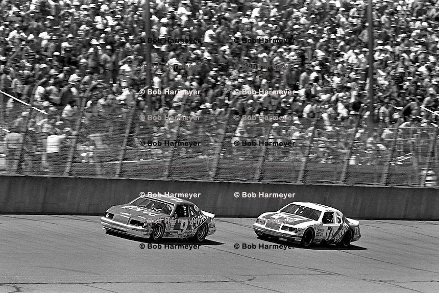 BROOKLYN, MI - AUGUST 11: Bill Elliott drives the Harry Melling Ford ahead of Kyle Petty in the Wood Brothers Ford en route to victory in the Champion Spark Plug 400 NASCAR Winston Cup race at the Michigan International Speedway near Brooklyn, Michigan, on August 11, 1985.