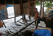Tiaon Bwere inside his house, trying to rescue parts of it whilst the waves of a 'king tide' demolish it, in the village of Betio on the Pacific island of Kiribati. The islands, and their way of life, are endangered by rising sea water levels which are eroding the fragile atoll, home to approximately 92,000 people.