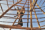 Mawa Santos works on his roof in the Southern Sudan village of Limbe. Santos and his neighbors have returned home from refuge in Uganda to begin rebuilding their war-torn land.