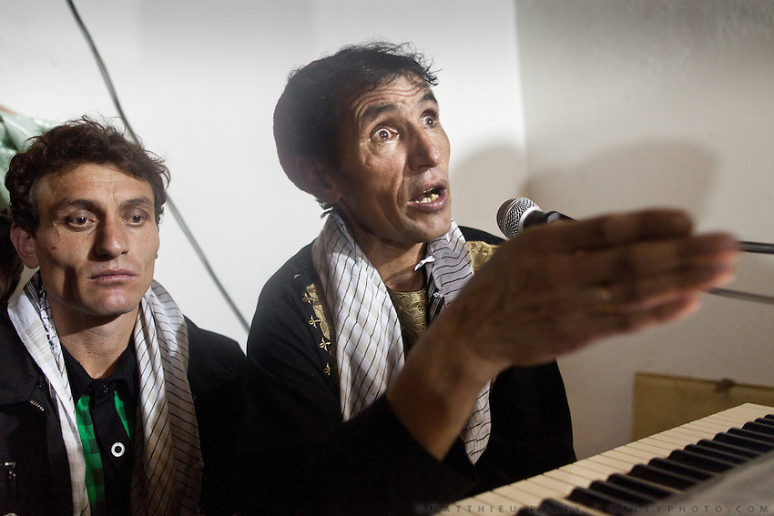 """The famed singer Mir Maftoon (translates from Farsi to """"King of Charms"""") who has played worldwide, performs at a local wedding. People dance. In the border town of Ishkashim, on the Tajikistan - Afghanistan border. Hindukush mountains."""
