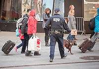 An NYPD counterterrorism officer with his K-9 partner sniffs at luggage in Times Square on Tuesday, March 22, 2016. Security in New York has been heightened in the wake of the terrorist bombings in Brussels, Belgium. (© Richard B. Levine)